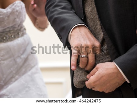 a portrait of process of wedding where man takes off a wedding ring from his pocket
