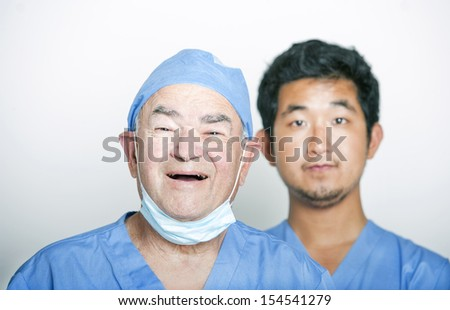 A portrait of Senior adult surgeon and a young Asian doctor - stock photo