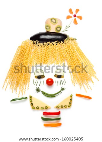 A portrait of shy clown made of vegetables and noodles. - stock photo