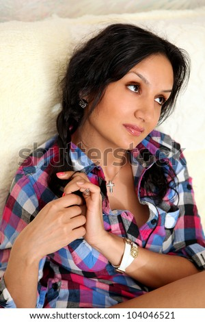 A portrait of the beautiful young dark-haired girl in pajamas chemise at home.