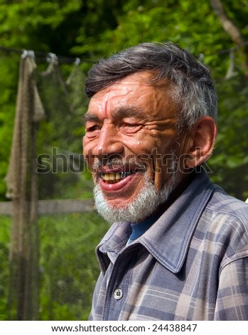 A portrait of the old weather-burned smiling man with grey beard.