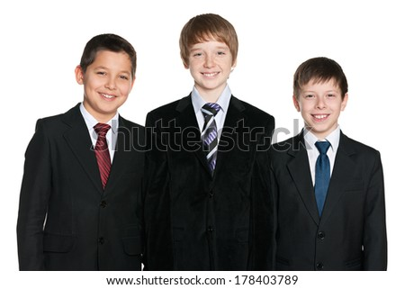 A portrait of three laughing young boys in black suits on the white background - stock photo