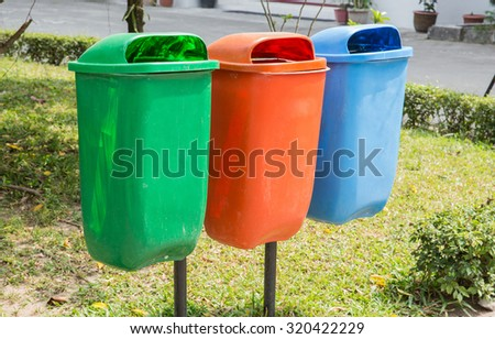 A portrait of three trash bin in different colors and purpose on a park
