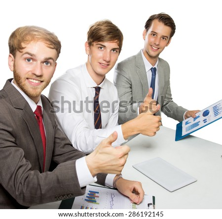 A portrait of three young businessman smiling with their thumbs up, isolated - stock photo