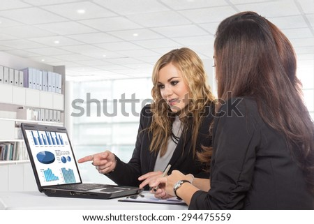 A portrait of  two friendly businesswomen sitting and discussing new ideas, isolated - stock photo