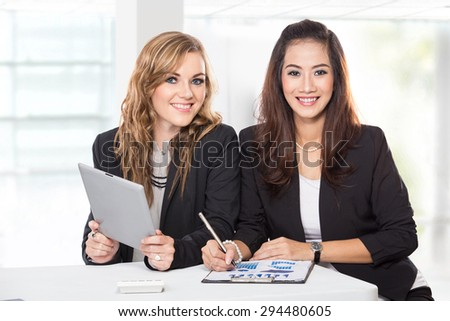 A portrait of  two friendly businesswomen sitting and discussing new ideas, isolated