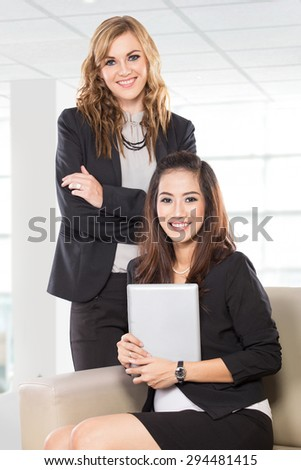A portrait of two young businesswoman sitting and standing next to each other, smiling. Isolated. - stock photo