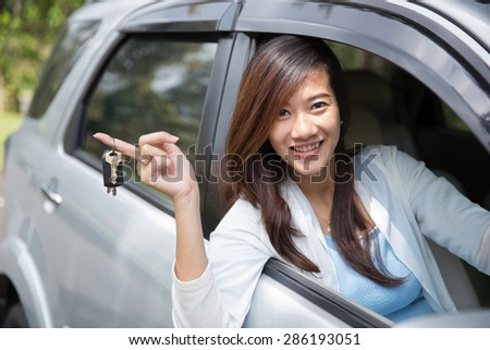 A portrait of Young asian woman holding a key car on her finger outside the window - stock photo