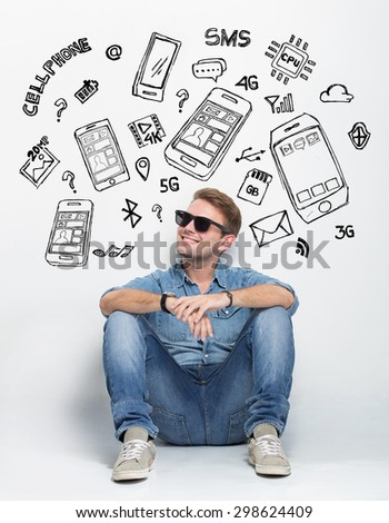 A portrait of Young caucasian man wear sunglasses while sitting on the floor thinking about having a new smartphone - stock photo
