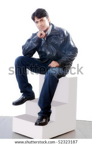 a portrait of young Indian man sitting on steps wearing leather jacket and blue jeans