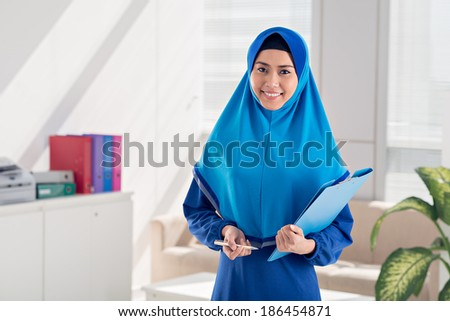 A portrait of young Muslim business lady standing with a folder - stock photo