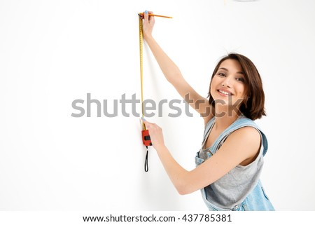 A portrait of young pretty girl, in gray shirt and denim overall, measuring the wall with tape, looking at camera, isolated on white background - stock photo