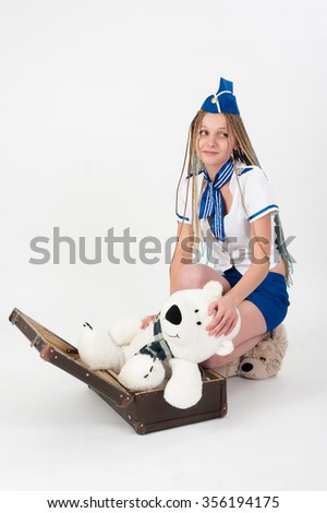 A portrait picture on lovely young attractive woman with long braid hair in stewardess uniform packs toy bear in vintage suitcase over white background - stock photo