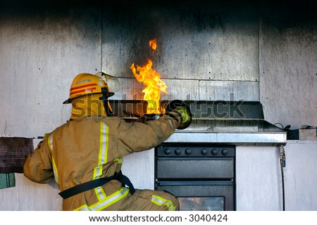 A pot full of cooking oil on fire being put out by a firefighter. - stock photo