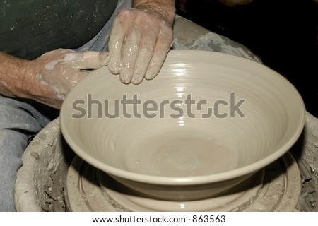 A potter throws his 20th bowl of the day - stock photo