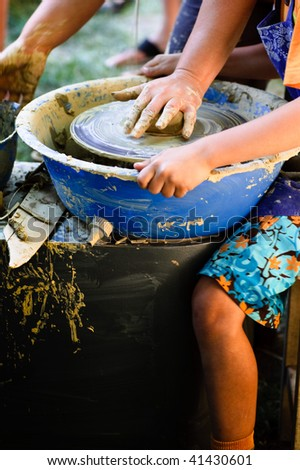 A potters hands guiding a child hands to help him to work with the ceramic wheel - stock photo