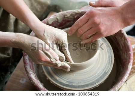 A potters hands guiding pupil hands to help him to work with the ceramic wheel