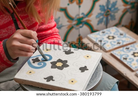 A pottery decorator painting a ceramic tile with floral motifs in his work table in Caltagirone, Sicily - stock photo