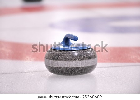 A 40 pound granite stone known as the 'Rock' rests outside of the target on a sheet of pebbled ice, in the sport and game of Curling. - stock photo