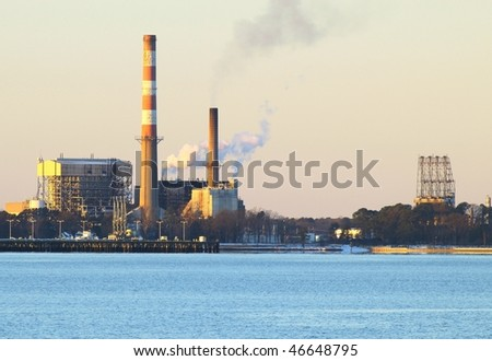 A power plant on the york river spewing pollution into the atmosphere - stock photo