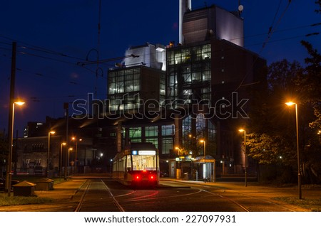 A power plant with a big chimney behind a tram station at sunset - stock photo