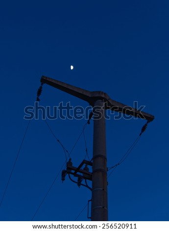 A Power Pole with the moon at night