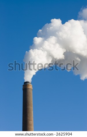A power station chimney spewing out smoke steam and pollution.