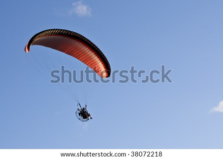 A powered paraglider in flight. Paragliding is also known as paramotoring. - stock photo
