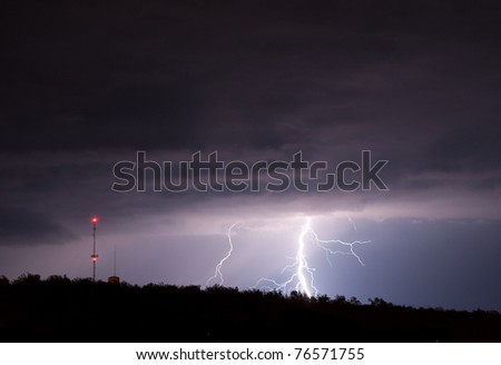 A powerful and electric spring thunderstorm lights up the night sky and drops record rainfall. - stock photo