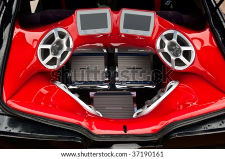 a powerful audio system with amplifiers speakers and lcd monitors in the car trunk - stock photo