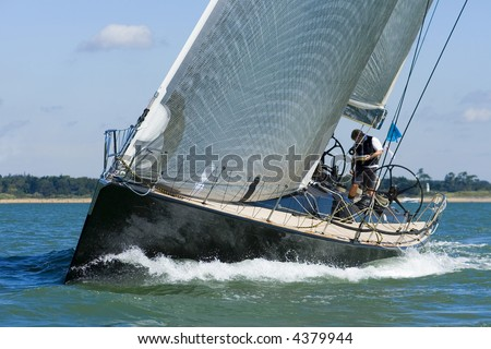A powerful black racing yacht with wind filled sails powers through coastal waters - stock photo