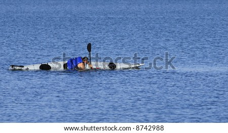 A powerful male kayaker performs float-asisted roll in calm waters of Mission Bay, San Diego, California. Copyspace on top and bottom.