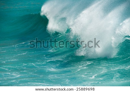 A powerful turquoise ocean wave breaking on shore - stock photo