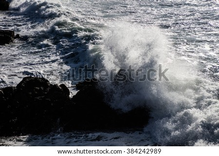 A powerful wave crashes on rocks along the scenic coast of northern California. Wave energy continually shapes coastlines all over the world. - stock photo