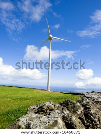 A powerful windmill generating clean renewable energy. Azores coastline