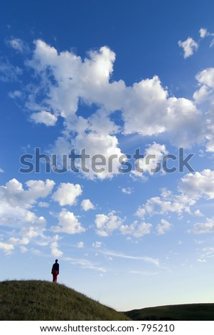 A prairie landscape with large sky and a person walking in the grass. - stock photo