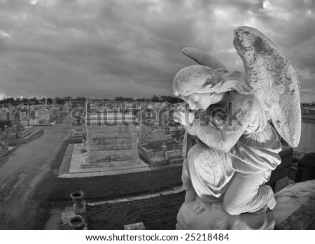 A praying statue kneels on top of a tomb in New Orleans under moody skies.  High point of view to contain the cemetery landscape in the background. - stock photo