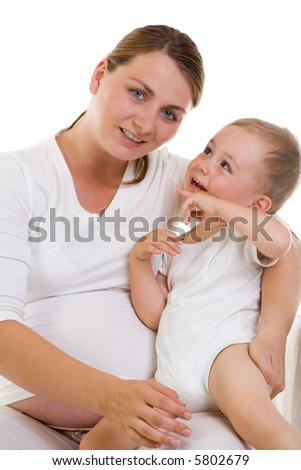 A pregnant caucasian woman with her happy smiling baby son, both wearing white with white background. Planned parenthood and childcare. Lineage. - stock photo