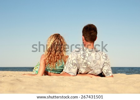 A Pregnant couple in love on the beach - stock photo