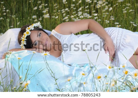 A pregnant girl  lies on the bed in a field of flowers