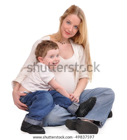 A pregnant mother and her toddler son are sitting on a white isolated background. They are wearing jeans and look happy.