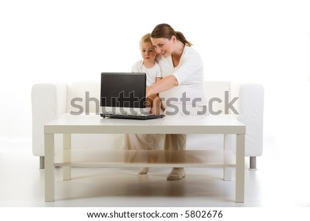 A pregnant mother sits with her young son in front of a laptop computer, showing him something on the screen. Picture in white theme. - stock photo