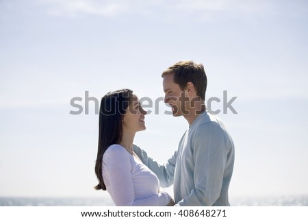 A pregnant woman and her partner embracing on the beach - stock photo