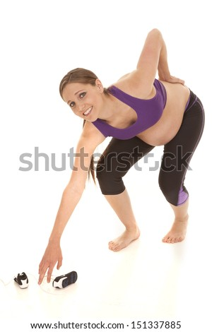 A pregnant woman is bending over in pain. - stock photo