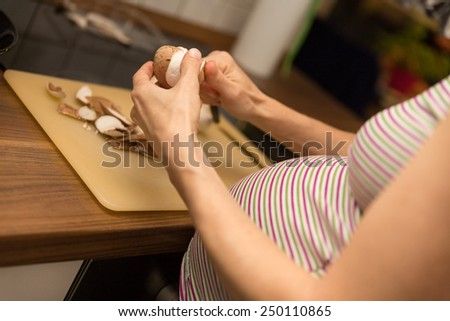a pregnant woman is cutting mushrooms in the kitchen - stock photo