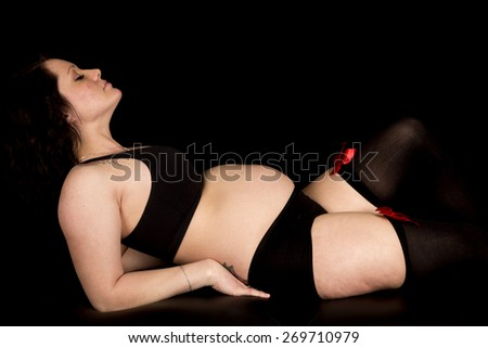 a pregnant woman laying back in her sexy outfit with a tattoo on her back and shoulder. - stock photo