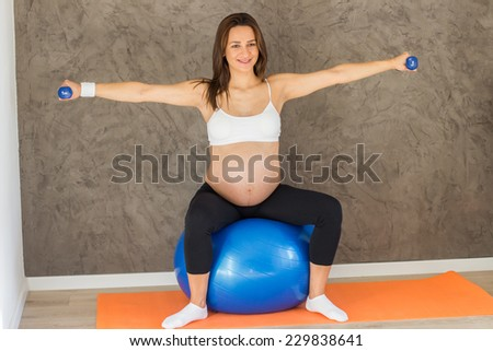 A pregnant woman lifting dumbbells while sitting on an exercise ball - stock photo