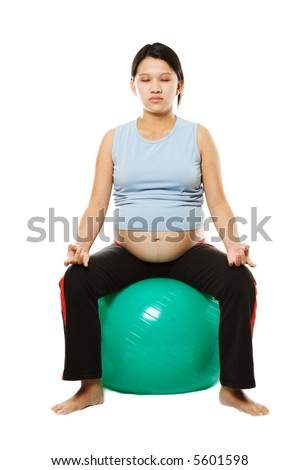A pregnant woman mediitating on an exercise ball