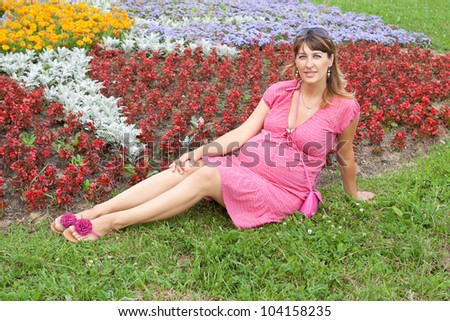 A pregnant woman (9 months) rests in a park - stock photo