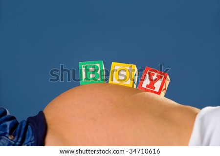 A pregnant woman's belly is holding wood alphabet blocks. - stock photo